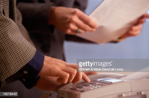 SENDING INFORMATION ON FAX MACHINE : Stock Photo