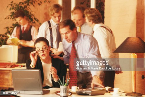 BUSINESSMAN AT DESK BY CO-WORKER : Stock Photo