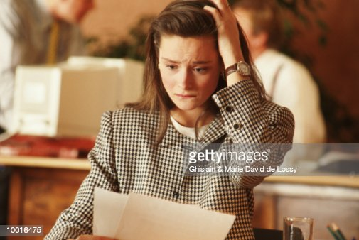 STRESSED BUSINESSWOMAN LOOKING AT PAPERS : Stockfoto