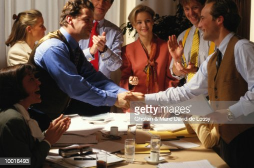 WORKERS SHAKING HANDS OVER CONFERENCE TABLE : Stock Photo