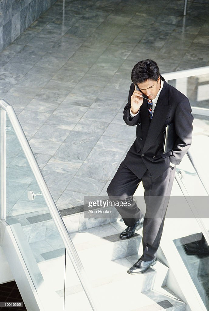 BUSINESSMAN ON PHONE ON OFFICE STAIRS : Stock Photo