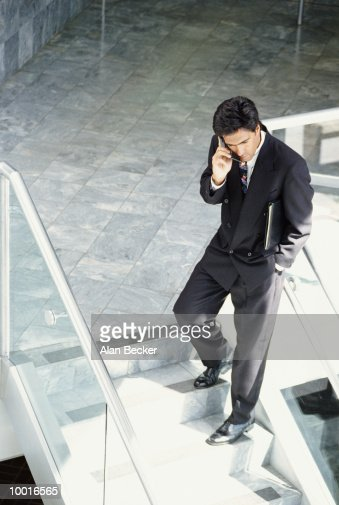 BUSINESSMAN ON PHONE ON OFFICE STAIRS : Stockfoto