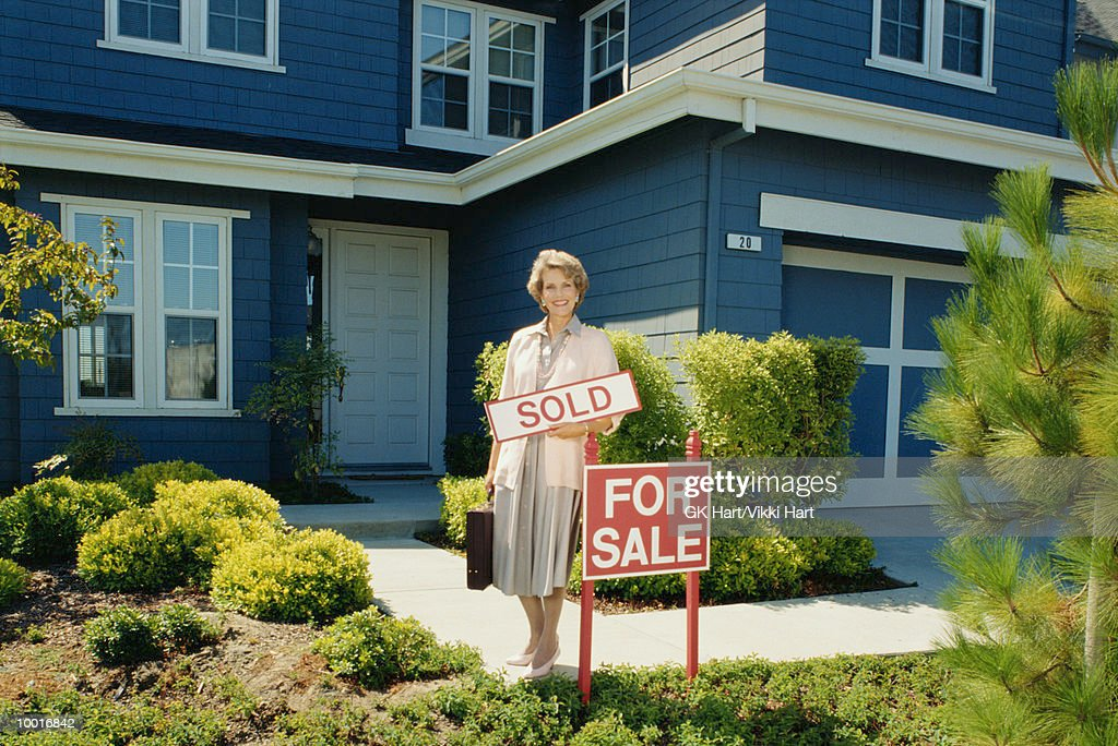 FEMALE REALTOR WITH SOLD SIGN IN FRONT OF HOME : Stockfoto