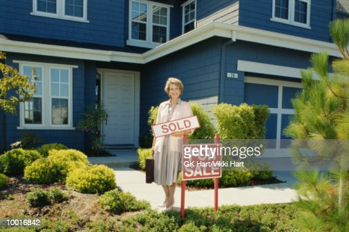 FEMALE REALTOR WITH SOLD SIGN IN FRONT OF HOME : Stock Photo