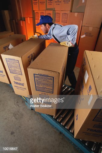 WORKER WITH BOXES IN FURNITURE WAREHOUSE : Stock Photo