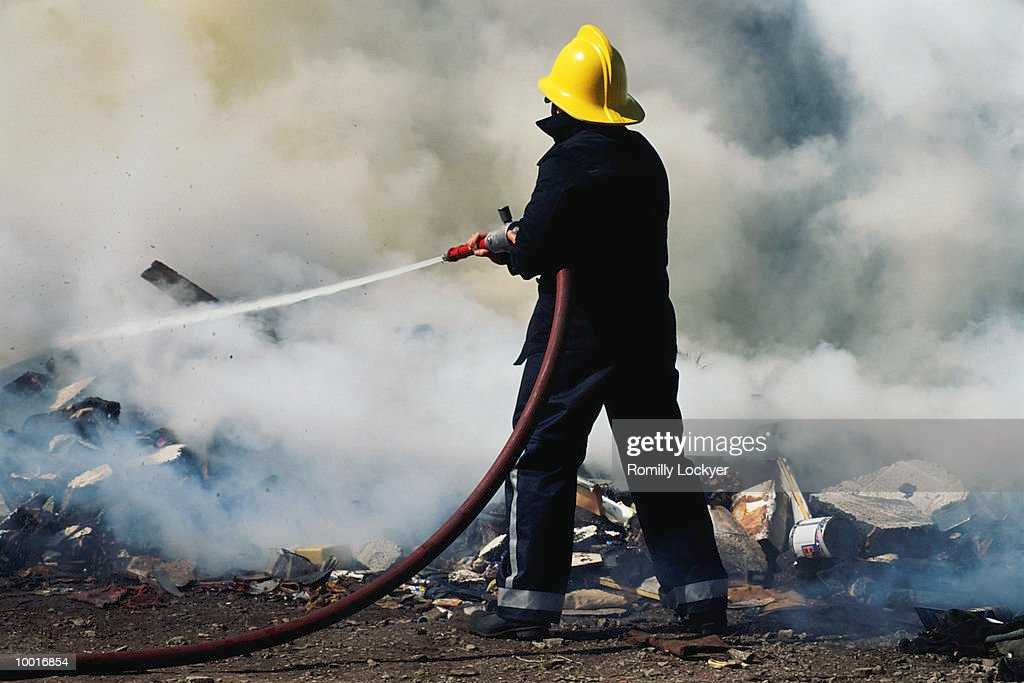 FIREMAN HOSING FIRE IN UNITED KINGDOM : Stock Photo