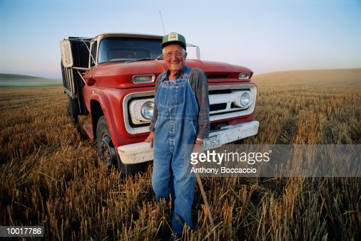 ELDERLY FARMER WITH CANE AND TRUCK IN FIELD IN WASHINGTON : Stockfoto