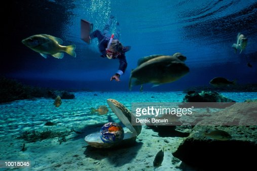 BUSINESSMAN SWIMMING TO WORLD IN OYSTER : Stockfoto