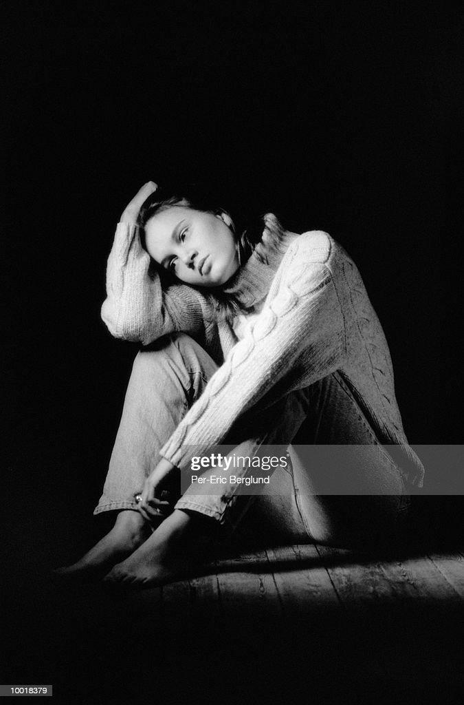 YOUNG WOMAN SITTING ON FLOOR : Stockfoto
