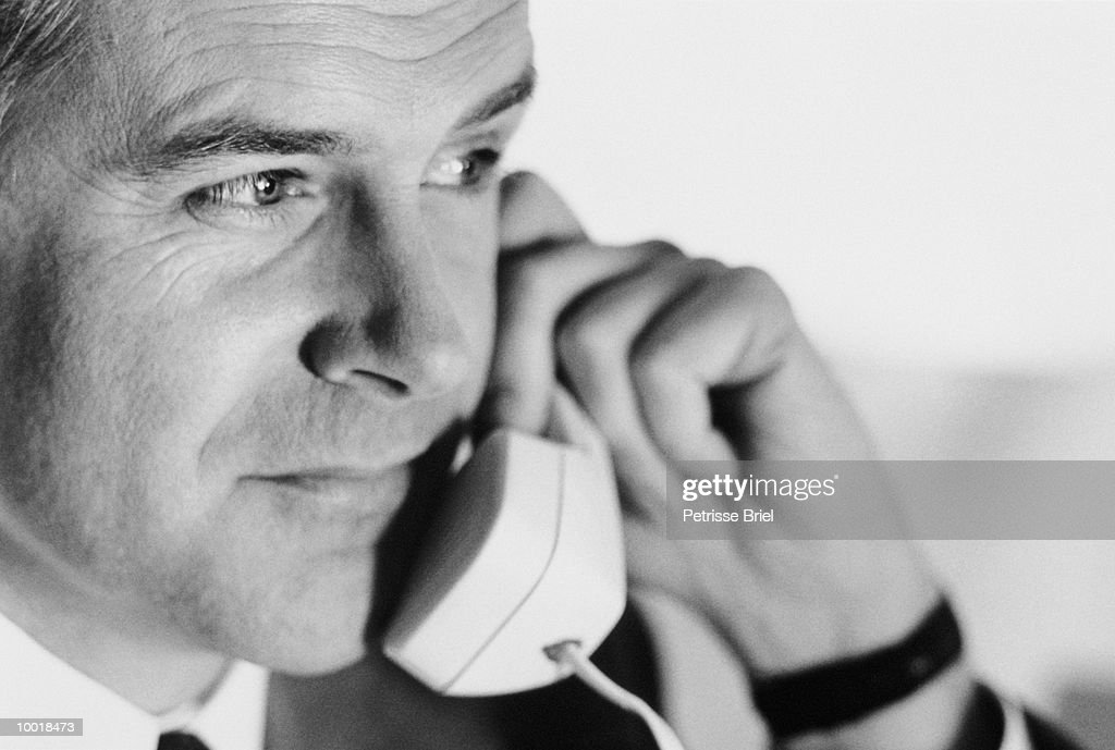 CLOSE-UP OF A BUSINESSMAN ON PHONE IN BLACK AND WHITE : Stockfoto