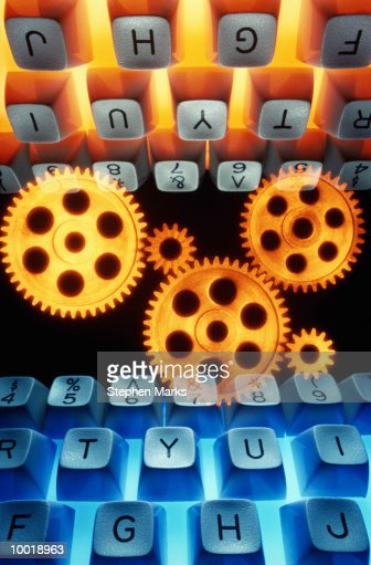 GEARS BETWEEN TWO KEYBOARDS : Stock Photo