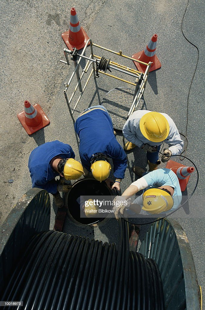 CREW LAYING ELECTRICAL CABLE : Stockfoto