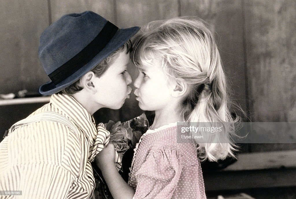 LITTLE GIRL & BOY SWEETHEARTS KISSING : Stock Photo