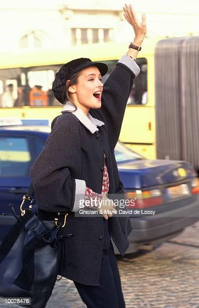 WOMAN ON SIDE OF STREET WAVING