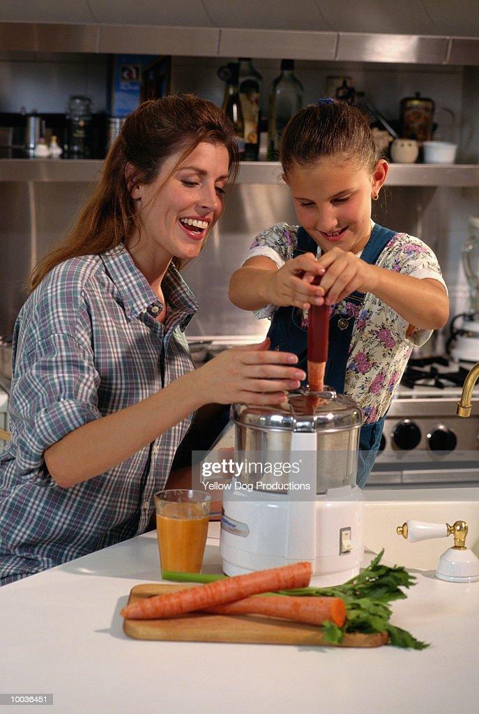 MOM & DAUGHTER MAKING VEGETABLE JUICE : Stock Photo