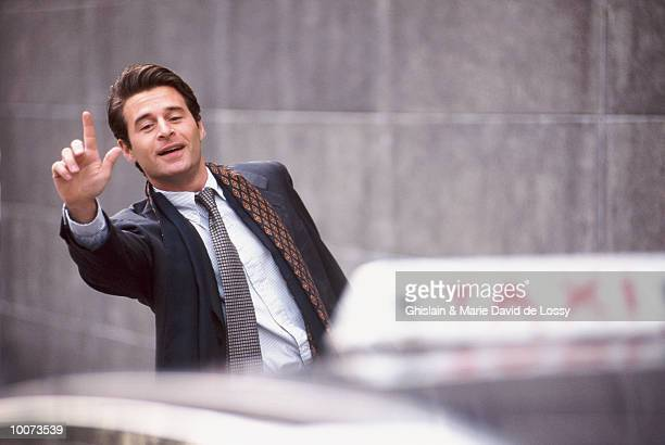 BUSINESSMAN HAILING TAXI