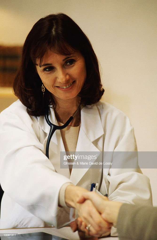 WOMAN SHAKING HANDS WITH A FEMALE DOCTOR : Stock Photo