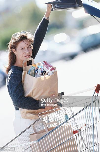 WOMAN WITH GROCERY CART IN PARKING LOT
