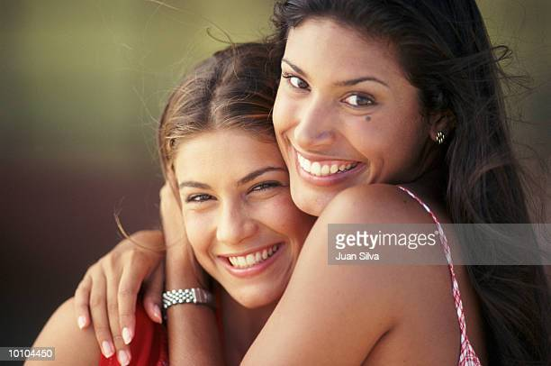 2 YOUNG WOMEN SHARING A MOMENT OUTDOORS