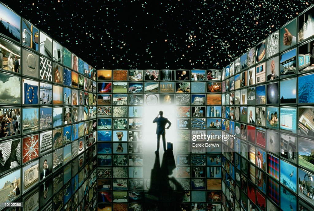 MAN IN ROOM FILLED WITH TELEVISION SCREENS : Stock Photo