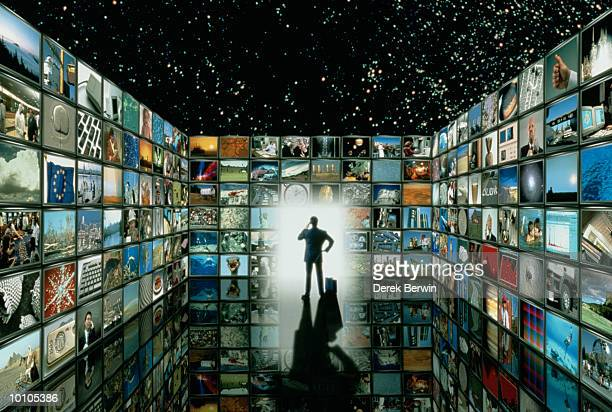 MAN IN ROOM FILLED WITH TELEVISION SCREENS