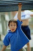 BOY AGE 7 WITH MONKEY BARS ON PLAYGROUND
