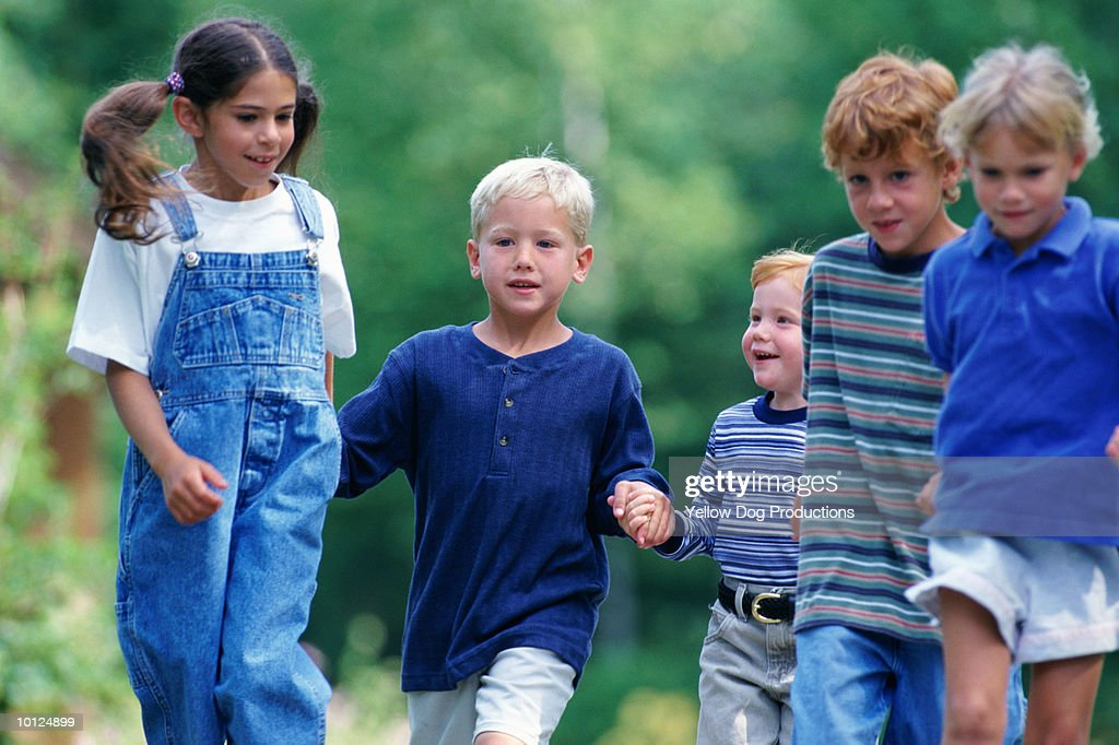 GROUP OF KIDS RUNNING DOWN THE ROAD : Stock Photo