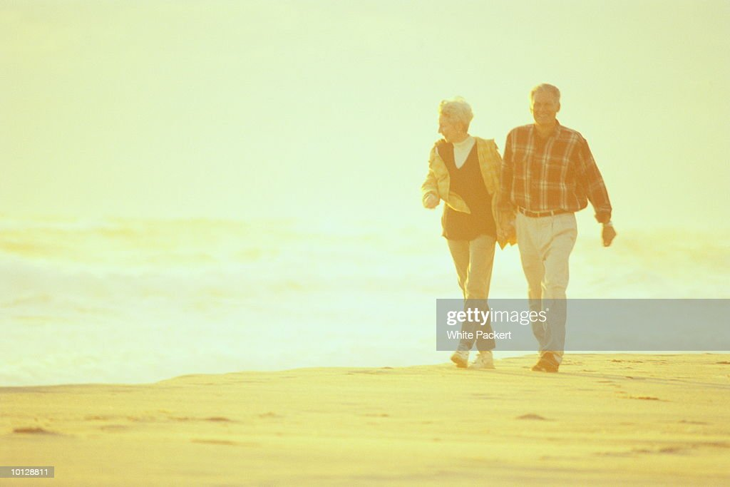 MATURE COUPLE WALKING ON BEACH- NANTUCKET : Stock Photo