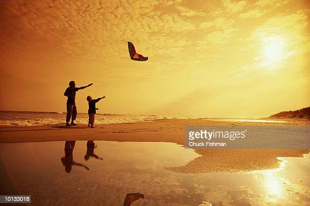 FATHER AND SON FLYING KITE ON BEACH, NEW YORK