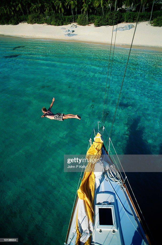 DIVING FROM SAILBOAT BOW, VIRGIN ISLANDS : Stock Photo