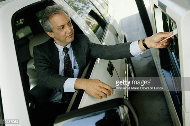 BUSINESSMAN AT CASH MACHINE