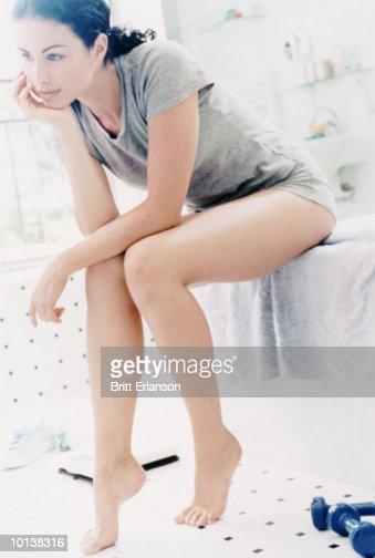 WOMAN SITTING ON THE EDGE ON BATH, RESTING : Stock Photo