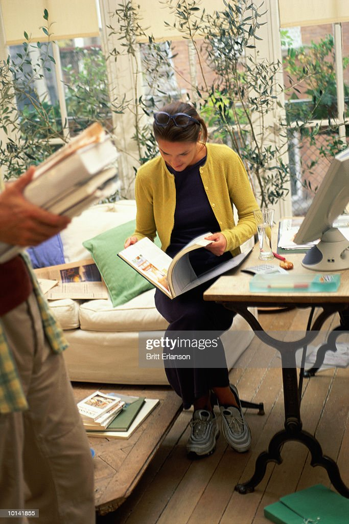WOMAN WITH BOOK AND COMPUTER AT HOME : Stock Photo