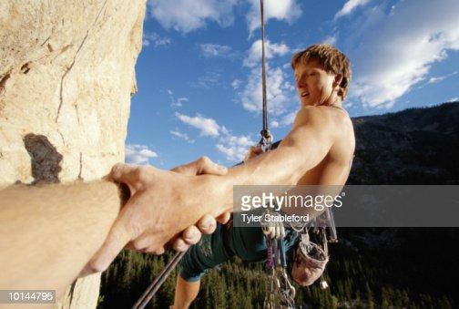 MALE CLIMBER REACHING FOR HAND, ASPEN, COLORADO