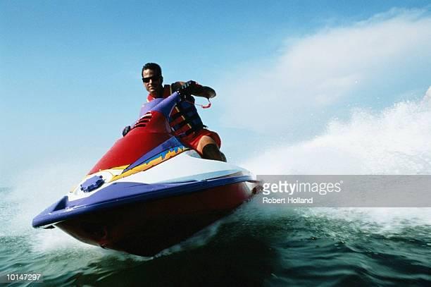 MAN SPINNING PERSONAL WATERCRAFT IN OCEAN