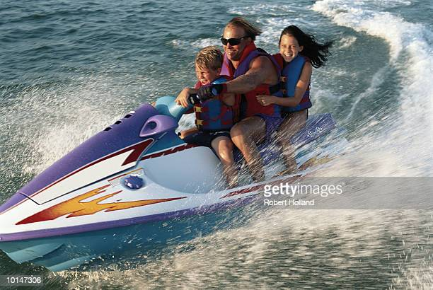 COUPLE ON PERSONAL WATERCRAFT IN OCEAN
