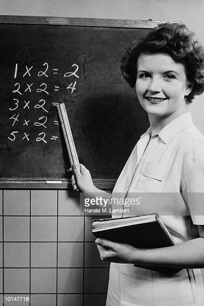 SCHOOLTEACHER POINTS TO MULTIPLICATION TABLE ON BLACKBOARD