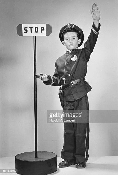 BOY AS TRAFFIC COP STANDING BY STOP