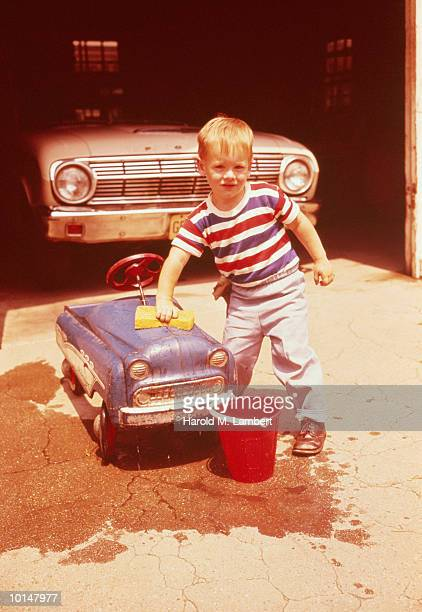 BOY WASHING HIS TOY CAR IN DRIVEWAY