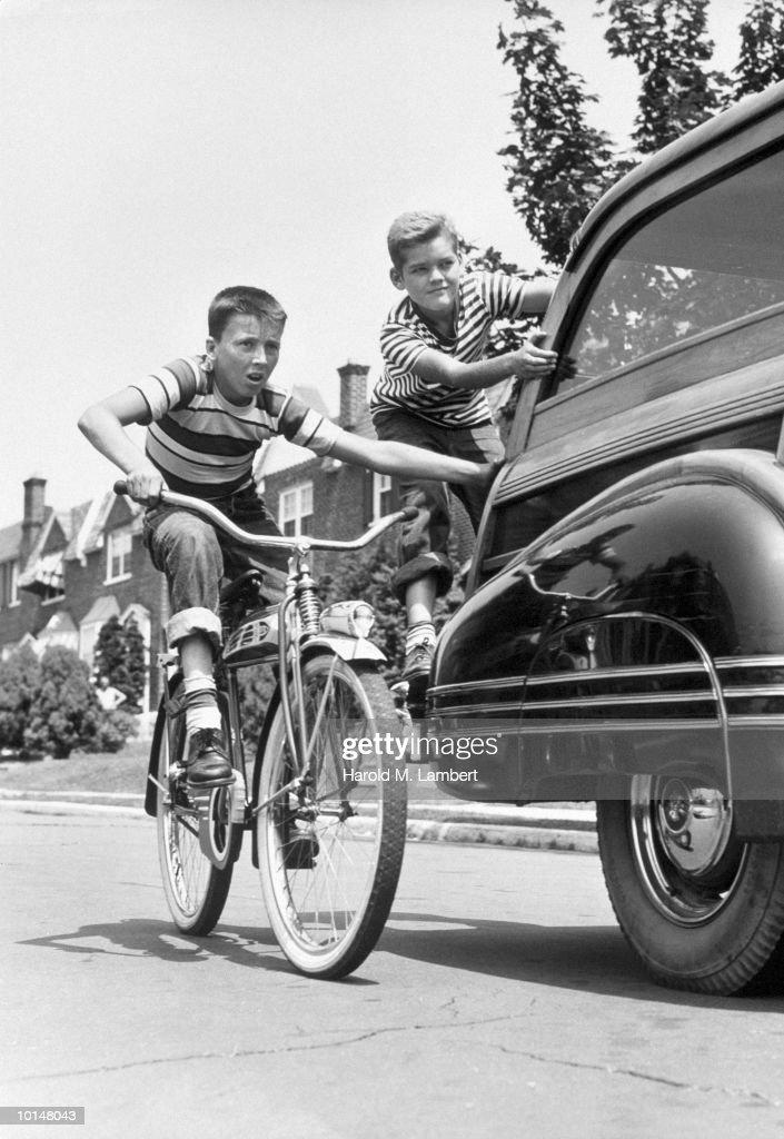 Thomas Cusick and Edward Langan hitching a ride on a car, circa 1955.