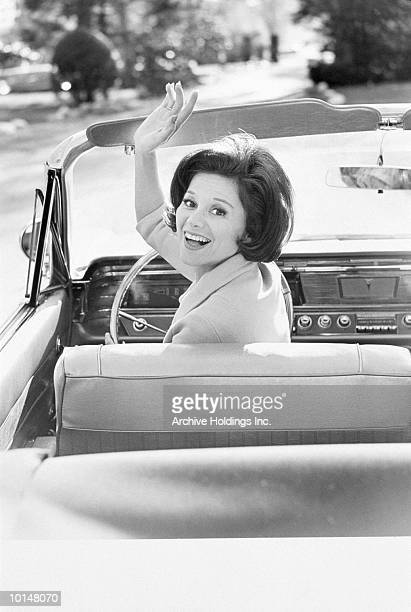 WOMAN IN CONVERTIBLE WAVES GOODBYE