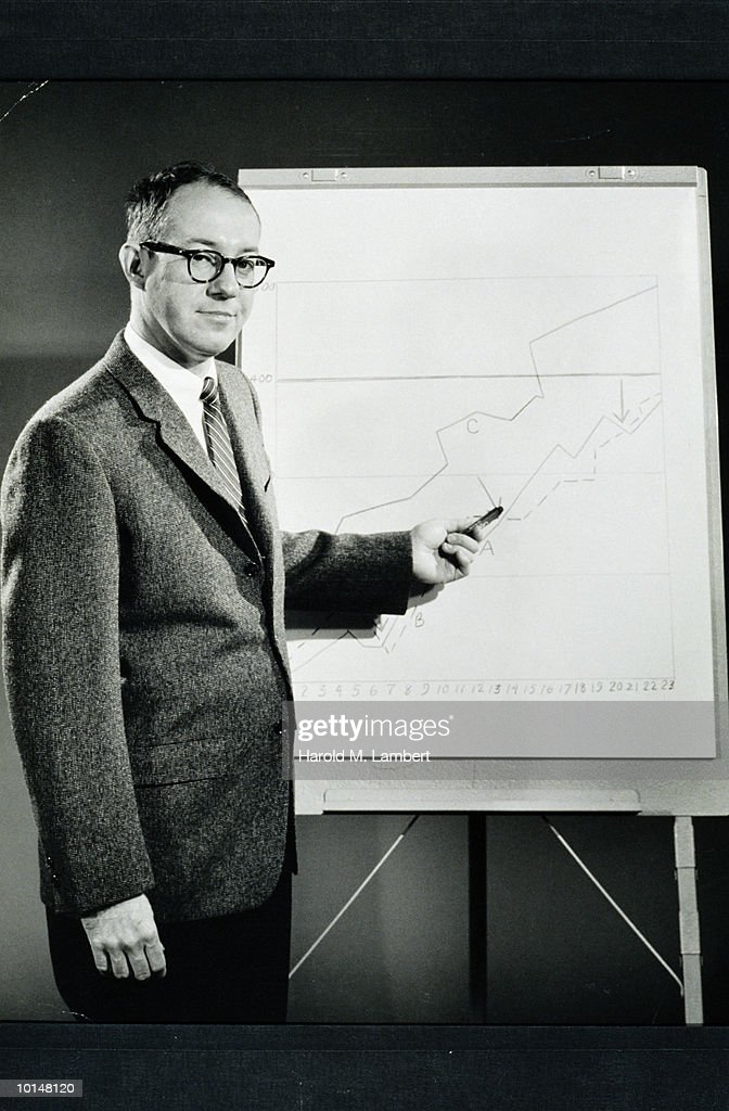 BUSINESSMAN POINTS TO A GRAPH ON A CHART : Stock Photo