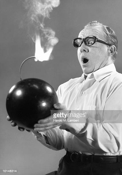 MAN HOLDING IGNITED BOMB, 1960S