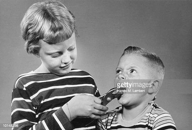 GIRL USING PLIERS TO PULL BOYS TOOTH