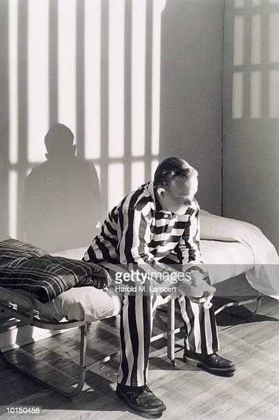 MAN IN JAIL CELL IN PRISON UNIFORM