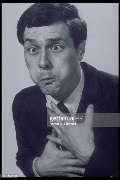 MAN HOLDING CHEST & PUFFING CHEEKS, CIRCA 1960