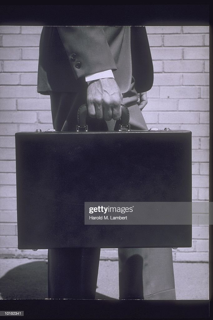 MAN HOLDING BRIEFCASE AT SIDE, CIRCA 1950S : Stockfoto