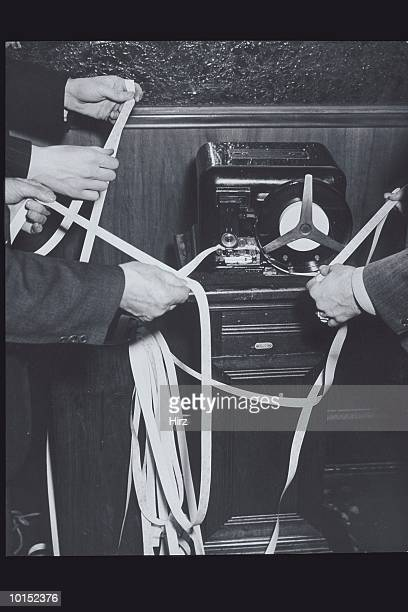 3 MEN READING TAPE AT TICKER