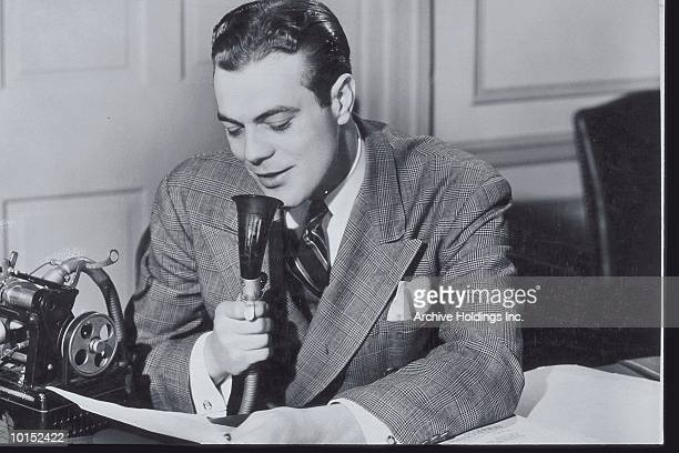 BUSINESSMAN READS INTO A DICTAPHONE
