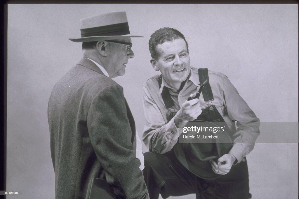 MAN IN OVERALLS TALKS TO MAN IN SUIT : Stockfoto